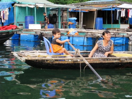 Children learn to steer a boat at an early age.